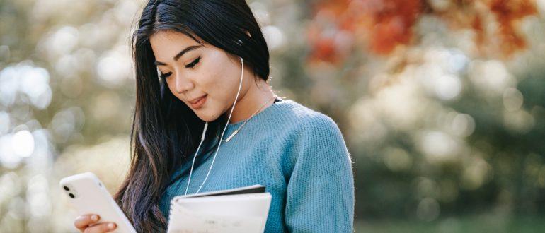 woman headphones cell phone notebook