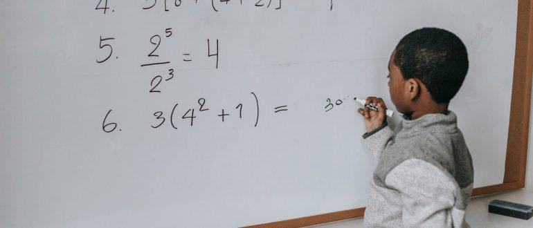 child doing algebra on whiteboard